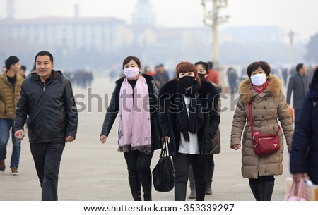 BEIJING, CHINA - DECEMBER 20, 2015: Unidentified people wear face mask at Tiananmen Square. Beijing issued a red alert for air pollution on Friday, its second red alert this month.    - stock photo