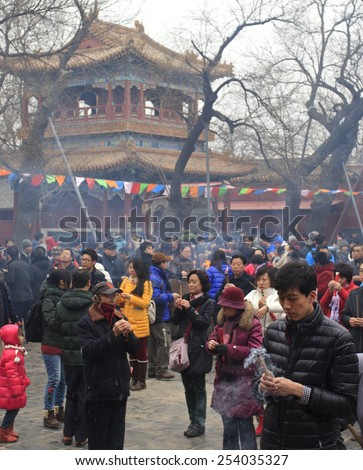 BEIJING, CHINA - FEBRUARY 19, 2015: People pray at Yonghegong Lama Temple on the first day of the Chinese Lunar New Year, the year of the sheep, which started on February 19 this year.   - stock photo
