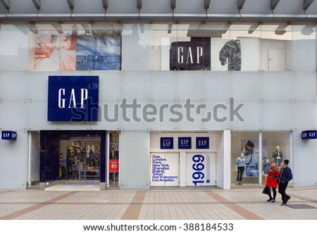 BEIJING, CHINA-FEBRUARY 21, 2016: Unidentified people walk nearby a Gap store; Gap is an American multinational clothing and accessories retailer. It operates more than three thousand stores worldwide - stock photo