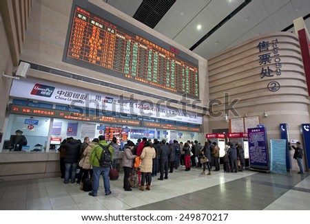 BEIJING,CHINA-JAN. 29, 2015: Passengers buy their tickets  at the Beijing South Railway station. Around 2.807 billion trips are expected to be made by people during China's Spring Festival travel rush - stock photo