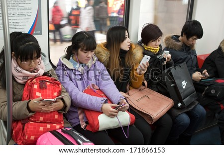 BEIJING, CHINA-JAN. 11,2014: Passengers use their mobile phones in a subway train. Mobile phones and tablets are used for people to entertain and view information when they take public transportation. - stock photo