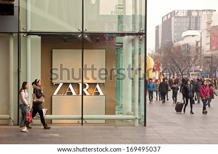 BEIJING, CHINA - JANUARY 2, 2014: People is seen around a Zara store. Zara is one of the largest international fashion companies and it's the flagship chain store of the Inditex group. - stock photo