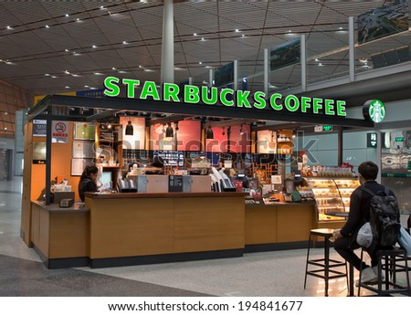 BEIJING, CHINA - JANUARY 23, 2014: People is seen at a Starbucks store. Starbucks is the largest coffeehouse company in the world, with 20,891 stores in 64 countries including 851 in China. - stock photo