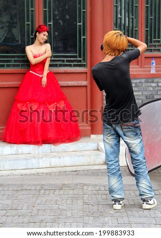 BEIJING, CHINA - JUL 5, 2011: Young stylish photographer taking a picture of a beautiful girl in red dress for wedding portfolio on a bacground of traditional chinese building - stock photo