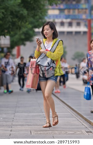 BEIJING, CHINA -JUNE 9, 2015. Fashionable young girl busy with her smartphone. China has currently 519.7 million smartphone users. That figure will rise to 574.2 million Chinese smartphone users by 2015. - stock photo