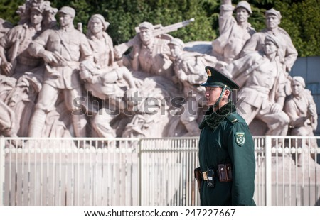 BEIJING, CHINA - MARCH 27: Chinese soldier stands on attention in front of revolutionary statu next to Mausoleum of Mao Zedong at Tiananmen Square on March 27, 2013 in Beijing - stock photo