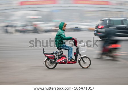 BEIJING, CHINA - MARCH 31: Chinese teen rides on motor scooters on a busy street in Dongcheng District on March 31, 2013 in Beijing - stock photo