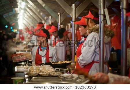 BEIJING, CHINA � MARCH 27: Food sellers sells snacks on Donghuamen Night Market - nighttime snack street on the northern end of Wangfujing Street on March 27, 2013 in Beijing - stock photo