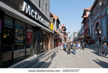 BEIJING, CHINA - MARCH 27: people walks next to McDonald's restaurant at one of the renovated perpendicular street to famous Qianmen Dajie pedestrian commercial street on March 27, 2013 in Beijing - stock photo