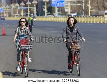 BEIJING, CHINA - MARCH 27, 2016: Two unidentified women ride bicyle near Tiananmen square. Beijing government's  plans to include more bike lanes for helping to reduce city smog. - stock photo