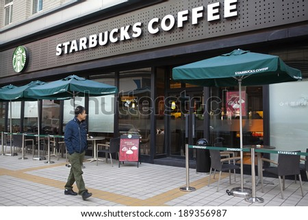 BEIJING, CHINA - NOV 10, 2013: A man is seen walking nearby a Starbucks coffee store. Starbucks is the largest coffeehouse company in the world, with 20,891 stores in 64 countries - stock photo