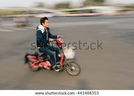 Beijing, China - October 18, 2015: Young man riding an Electric bike in Beijing, China.  - stock photo