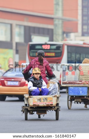 BEIJING-DEC. 5. Young boy in a freight bike. Human powered freight tricycles or cargo bikes are still a very popular daily transport mode in many congested Chinese cities. Beijing, December 5, 2012. - stock photo