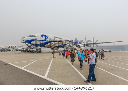 BEIJING JULE 30, Passengers get off from Air Chaina at Beijing airport on June 30, 13,in Beijing. The airport has registered 488,495 annually aircraft movements and ranked 10th in the world. - stock photo