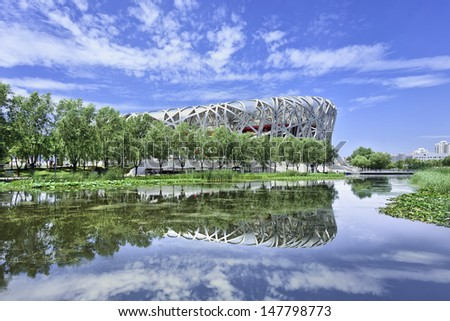 BEIJING-JULY 28. Bird's Nest mirrored in a pond. The Bird's Nest is a stadium in Beijing, China, designed for use throughout the 2008 Summer Olympics and Paralympics. Beijing, July 28, 2013.   - stock photo