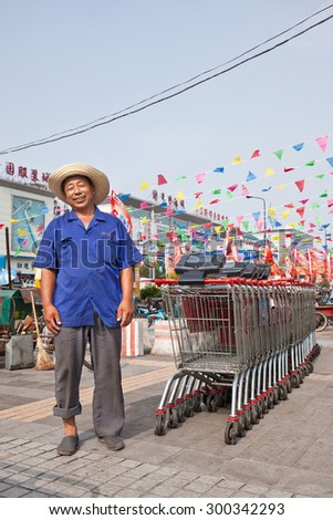 BEIJING-JULY 24, 2015. Cheerful elder Wu Mart employee with caddy row. China's elderly can hardly find suitable work and they often accept low salary jobs with monthly wages of 1,500 to 2,000 RMB.  - stock photo