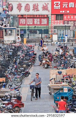 BEIJING-JULY 10, 2015. Man with bicycle leaves a parking. Although rapid multiplication of cars in China the bicycle remains the biggest means of individual mobility for hundreds of millions Chinese. - stock photo