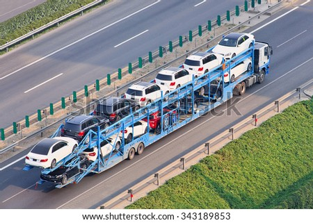 BEIJING-JULY 7, 2015. Over sized carrier with Mercedes cars. These illegal car trailers have lengths up to 40m. They are prohibited enter urban areas and load trailers outside Beijing fifth ring road. - stock photo