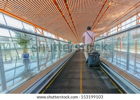 BEIJING- JULY 5: Passenger walking on the speedwalk at Beijing airport on July 5, 13 in Beijing . The airport has registered 488,495 annually aircraft movements and ranked 10th in the world. - stock photo