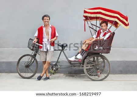BEIJING-JULY 28. Rickshaw drivers having a break. Rickshaw is the most popular form of transportation for tourists who want to explore the ancient hutongs in Beijing old town. Beijing, July 28, 2010 - stock photo