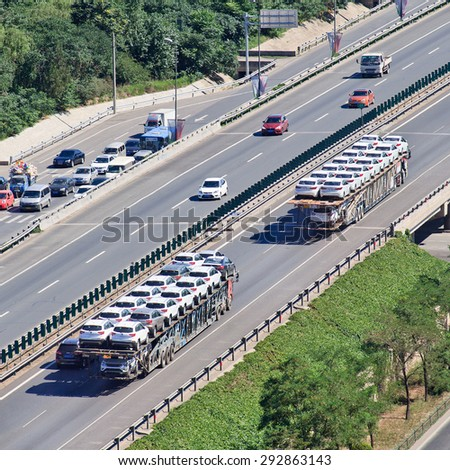 BEIJING-JUNE 30, 2015. Over sized car carrier. 16.5m is China's official truck length, but a large number of carriers simply flout the rules and factor fines into their rates and charges to customers. - stock photo