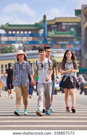 BEIJING-JUNE 9, 2015. Young lovers hand in hand. According 2010 national census, China's unmarried population is huge: about 249 million 18-and-older Chinese are not married (18.6% of population). - stock photo
