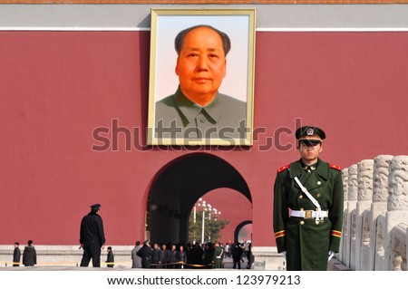 BEIJING - MARCH 11:Chinese soldier stands guard in front of a portrait of Mao Zedong in Tiananmen square on March 11 2009 in Beijing,China. Chairman Mao Zedong is still being worshiped all over China. - stock photo
