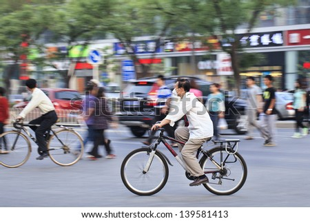 BEIJING-MAY 24. Cyclist on street with mouth cap. Beijing residents take precautions against air pollution, often measured by US embassy as 'very unhealthy'?? or 'hazardous'??. Beijing, May 24, 2013. - stock photo