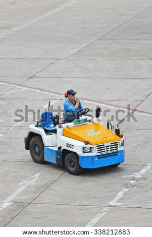 BEIJING-MAY 23. 2014. Nissan tow tractor for baggage dolly transport on Beijing Airport. Speed, efficiency, and accuracy are essential in ground handling services to minimize the turnaround time. - stock photo