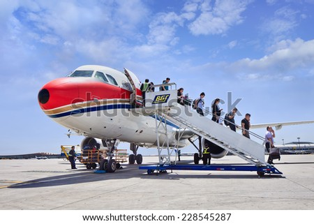 BEIJING-MAY 27, 2014. Passengers come out airplane on Beijing Airport. China's economy is now the world's second biggest and amid population of over 1.3 billion, a growing middle class want to travel. - stock photo
