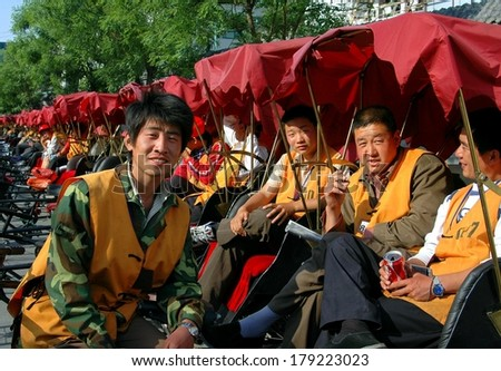 BEIJING - MAY 5, 2005:  Pedicab bicycle drivers sitting in their taxis waiting for fares at the Shi Sa Hai Hutong - stock photo