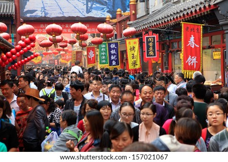 BEIJING - OCT 4: People crowd famous Wangfujing snack street during National Day holiday on Oct. 4, 2013 in Beijing, China. China's celebrates 64th anniversary of founding - stock photo