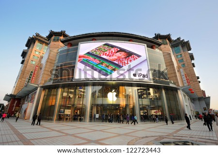 BEIJING - OCT 22: people walking in front of Apple store on Wangfujing street on October 22, 2012 in Beijing, China. This store just opened and is Asia's biggest Apple store with 2,300 square meters. - stock photo