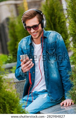 Being on my own wave. Happy young man in headphones holding mobile phone and smiling while sitting outdoors - stock photo
