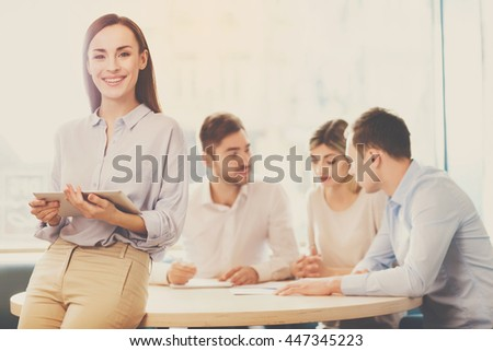 Being successful. Smiling and happy business woman standing in foreground with a tablet in her hands, her co-workers discussing business matters in the background - stock photo