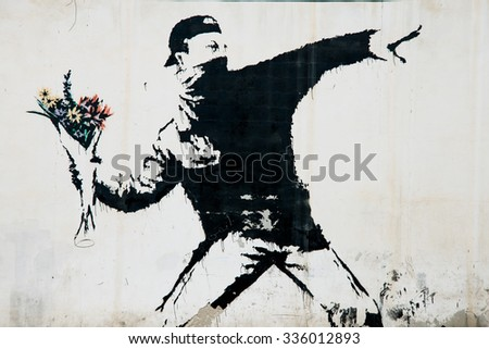 BEIT SAHOUR, OCCUPIED PALESTINIAN TERRITORIES - JUNE 18: A mural by the British street artist Banksy covers a wall in the West Bank village of Beit Sahour, June 18, 2014. - stock photo