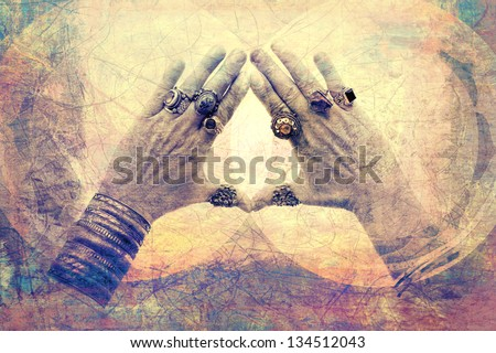 Bejeweled male hands opened from prayer into a frame of light. - stock photo
