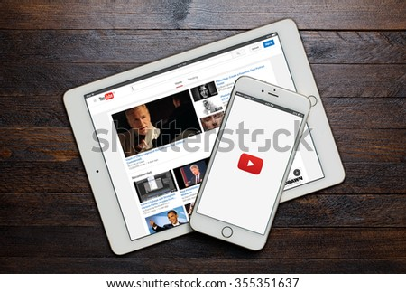 BEKASI, INDONESIA - DECEMBER 27, 2015: A loading screen of YouTube app on iPhone and a landing page of YouTube website on iPad. YouTube was founded by Chad Hurley, Steve Chen and Jawed Karim. - stock photo