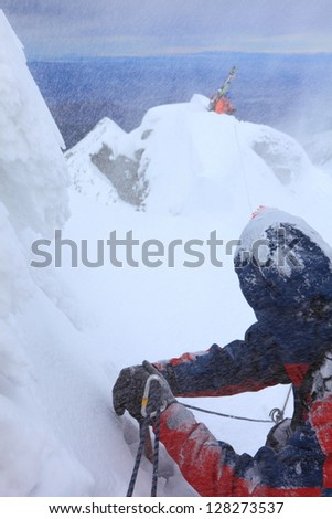 Belaying the lead while descending a steep narrow ridge in bad weather - stock photo