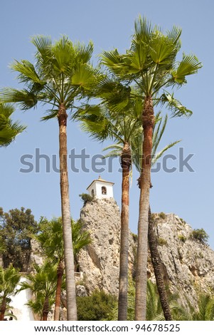 Belfry behind Palm Trees. This tower belongs to Alcozaiba fortress, built by muslims at XI century. Picture taken in El Castell de Guadalest, Alicante, Spain. - stock photo