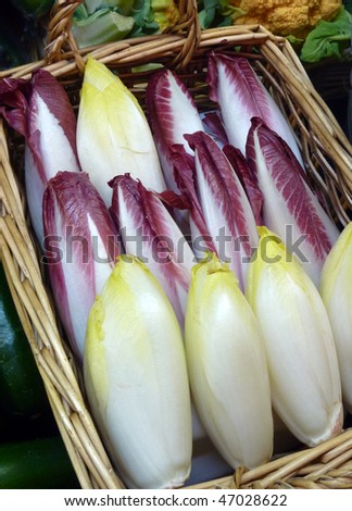 Belgian endives in basket at produce market - stock photo