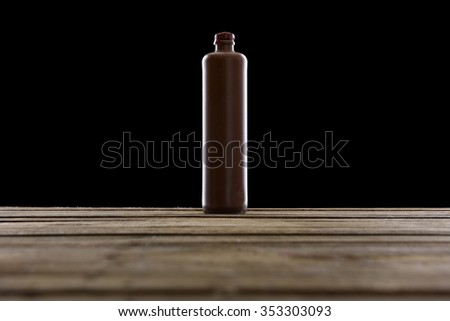 Belgian Gin Bottle in terracotta, black background - stock photo