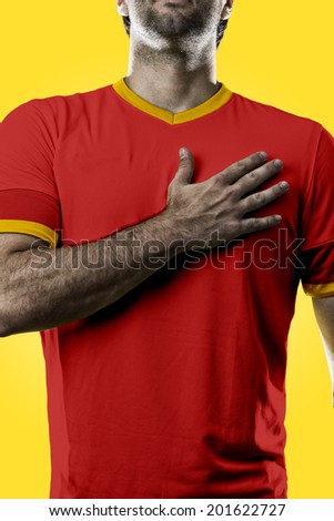 belgian soccer player, listening to the national anthem with his hand on his chest. On a yellow background. - stock photo