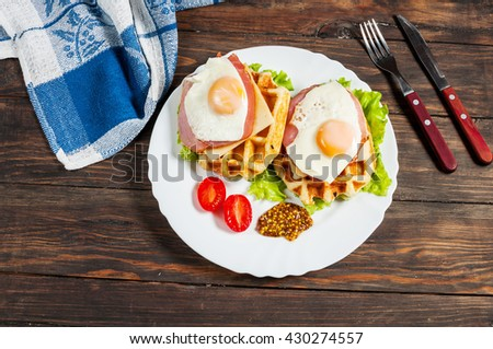 Belgian waffle with egg and salmon on wood table. - stock photo