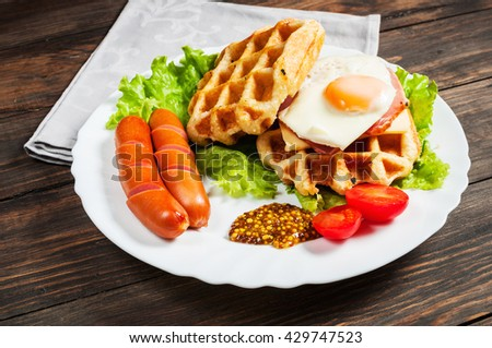 Belgian waffle with egg and sausage on wood table. - stock photo