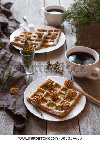 Belgian waffles sweet healthy dessert with honey, nuts, coffee and herbs. Bright morning mood food. Vintage wooden background, rustic kinfolk style. - stock photo