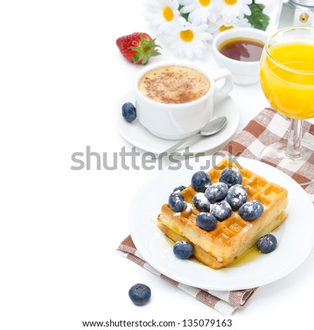 Belgian waffles with blueberries and strawberries, cup of cappuccino orange juice for breakfast isolated on a white background - stock photo