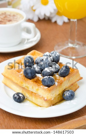 Belgian waffles with blueberries, coffee and orange juice for breakfast closeup vertical - stock photo
