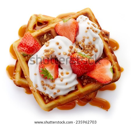 Belgian waffles with caramel sauce, whipped cream and strawberries isolated on white background (top view) - stock photo
