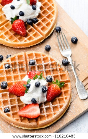 Belgian waffles with fresh fruit and sprinkled with icing sugar - stock photo